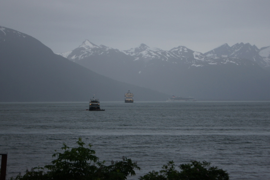 A ship goes by in the distance as two ships are leaving the harbor in the rain