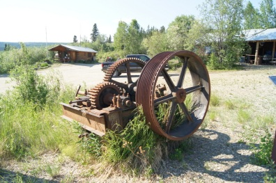 A display of old mining equipment in front of the Chicken Post Office